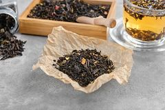 Dry tea leaves in parchment on table stock images