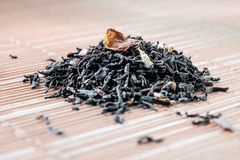 Dry tea leaves spread on light brown color background Stock Image