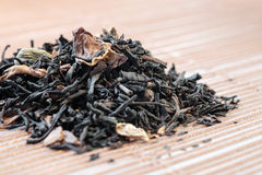 Dry tea leaves spread on light brown color background Royalty Free Stock Images