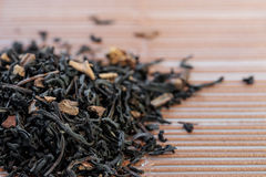 Dry tea leaves spread on light brown color background Stock Images