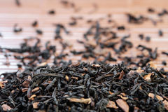 Dry tea leaves spread on light brown color background Stock Photo