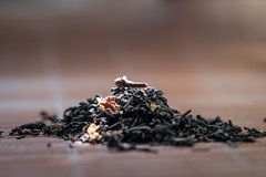 Dry tea leaves spread on light brown color background Royalty Free Stock Image