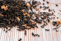 Dry tea leaves spread on light brown color background Stock Photography