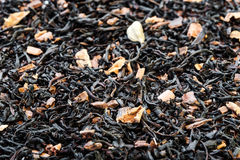 Dry tea leaves spread on light brown color background Stock Photos