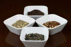 Dry tea leaves in square plates with reflection Royalty Free Stock Photography