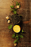 Dry tea with mint and lemon on wooden table Royalty Free Stock Photography