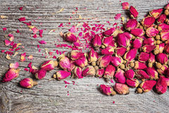 Dry tea rose buds on old wooden table Stock Photos