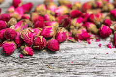 Dry tea rose buds on old wooden table Royalty Free Stock Photo