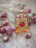 Dry tea roses and vintage perfume bottle on the old wood Stock Photos
