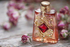 Dry tea roses and vintage perfume bottle on the old wood Royalty Free Stock Photo
