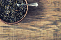 Dry tea in wooden plate on wooden table. Royalty Free Stock Images