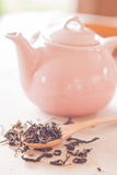 Dry tea in wooden spoon with ceramic jar Royalty Free Stock Image