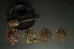 Dry teas and herbs collection. Dry tea and herbs collection of different types on black table royalty free stock photo