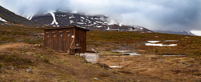 Dry toilets in a mountain camp. Wooden, dry toilet building in a mountain camp. There is a scooter path marked by red crosses leading from the camp towards Royalty Free Stock Images