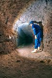 Dry tunnel, man worker in protective suite in underground. Mysterious dungeon tunnel Stock Image