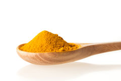Dry turmeric powder in wooden spoon on white background Stock Images