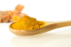 dry turmeric powder in wooden spoon on white background Stock Photo