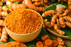 Dry turmeric in a wood bowl  with leaf and fresh turmeric Stock Image