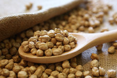 Dry and uncooked chickpeas in spoon and scattered Royalty Free Stock Image