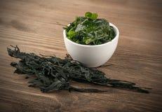 Dry Wakame Seaweed. Heap of Dry Wakame Seaweed on Wooden Background. Healthy Algae Food stock images