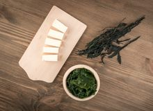 Dry Wakame Seaweed. On Natural Wooden Background. Healthy Algae Food with Soy Sauce and Tofu Top View Royalty Free Stock Images