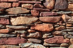 Dry wall. A wall of different colored natural building stones stock images