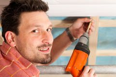 Dry waller with cordless screwdriver. Man doing dry walling, working under a roof slope Stock Photos
