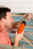 Dry waller with cordless screwdriver. Man doing dry walling, working under a roof slope Royalty Free Stock Photos