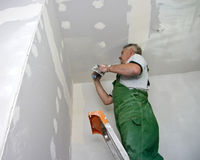 Dry waller at work. A dry waller standing on a ladder high at the ceiling, putting plaster on the walls with a special tool Royalty Free Stock Images