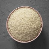 Dry white rice basmati in a pink bowl over concrete surface, top view. Flat lay, overhead, from above royalty free stock photo