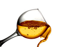 Dry white wine is poured into a glass. Dark Orange liquid, water, apple juice, white wine pouring into a glass, liquid in a speaker, isolated on a white Royalty Free Stock Images