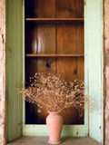 Dry wild field flowers in a vintage vase on a green window Stock Photos