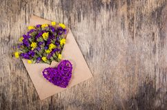 Dry wild flowers in a paper envelope and a wicker heart. Royalty Free Stock Photography