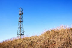 Dry Winter Grass and Comunication Tower Against Blue Sky Stock Photos