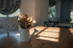 Dry yellow flower bouquet in the metal vase on wood table in the Royalty Free Stock Photography