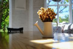 Dry yellow flower bouquet in the metal vase on wood table in the Royalty Free Stock Photos