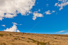 Dry yellow grass on hillside against blue sky. Hillside covered with dry yellow grass against blue sky with clouds Stock Photo