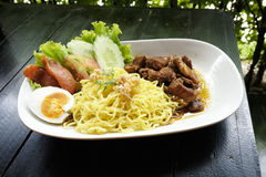 Dry Yellow Noodles with egg, salad, sausage and braised pork Stock Photo