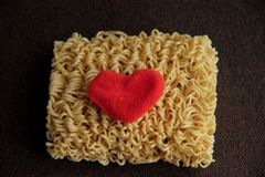 Dry yellow noodles and heart made of red fleece fabric on brown background close up and blurred. stock image