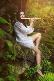 Dryad playing flute after the rain. Beautiful dryad playing flute in a forest after the rain. Romance and fantasy Stock Photo