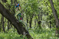 Dryad on the tree in a wild garden one with the green nature. The model from the conceptual body art Stock Photography