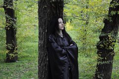 Dryad tree. Woman in black standing against a dark tree trunk in the green autumn forest Royalty Free Stock Images