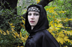 Dryad. Woman with diadem under black hood in the autumn forest Royalty Free Stock Images