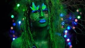 Dryade verte mystique effrontée dans la lumière noire de fluor UV avec les arbres rougeoyants sur le fond Concept d'imagination banque de vidéos