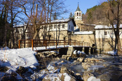 Dryanovo Monastery in the Winter. Famous Dryanovo monastery in Bulgaria, entrance from the river and the bridge covered with snow in the winter Stock Images