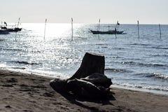 Dryftowy drewno zaciemnia widok łodzie zakotwiczać na morzu obrazy stock