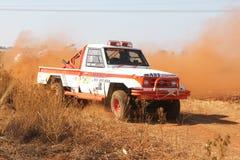 Dryfujący biały Toyota Landcruiser ciężarowy kopiący up pył na zwrocie Fotografia Stock