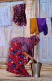 Drying. Overcast bowed woman drying linen hand washed in the yard of a rich antique house in india Royalty Free Stock Photography