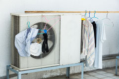 Drying by airconditioner heating unit. Drying clothed by airconditioner heating unit out side home Royalty Free Stock Image