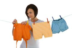 Drying baby clothes. Young smiling woman hanging clothes on clothesline using clothespin. Front view, white background. White background royalty free stock photos